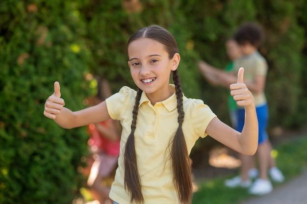 Mädchen mit zöpfen, die mit dem finger ein okay-zeichen zeigen