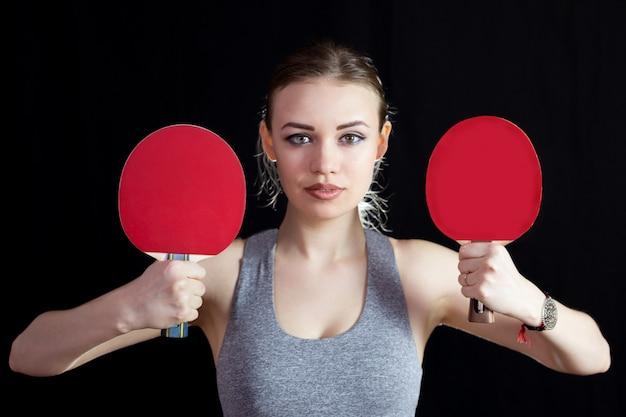 Mädchen mit zwei schlägern zum tischtennis spielen.