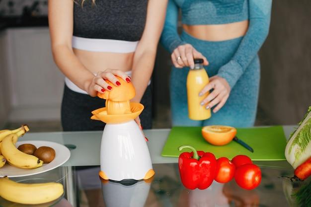 Mädchen mit zwei sportarten in einer küche mit gemüse
