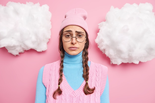 Mädchen mit zwei zöpfen hat einen düsteren ausdruck schmollend und die stirn runzeln fühlt sich enttäuscht oder verärgert trägt runde brille rosa hut rollkragen und weste posiert drinnen