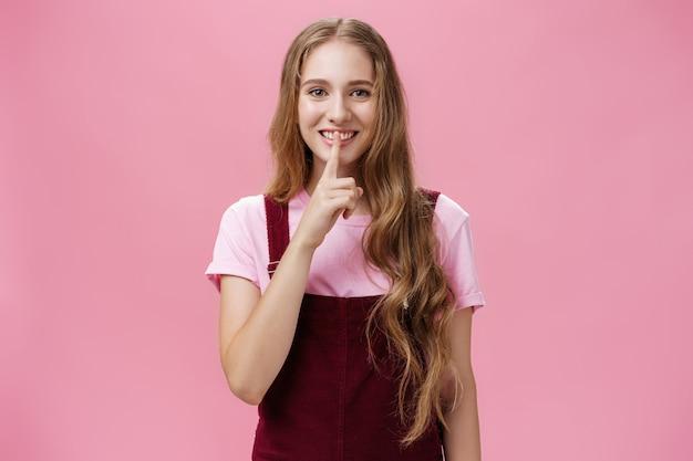 Mädchen möchte ihr schönheitsgeheimnis teilen, das knifflig und freundlich lächelt und eine leise geste mit dem zeigefinger zeigt ...