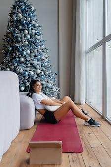 Mädchen nahe dem fenster, das gegen den hintergrund der weihnachtsdekoration aufwirft. weihnachten online-urlaub.