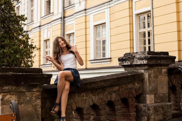 Mädchen nahe dem hight-schulgebäude. bildungskonzept, ende der schule. sommerferien