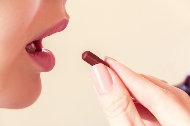 Mädchen nimmt eine pille mit dem mund