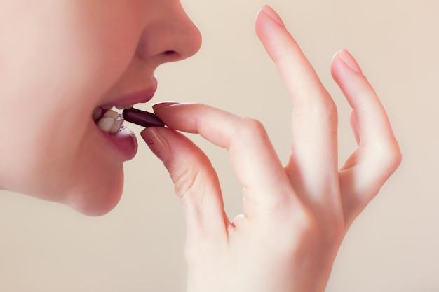 Mädchen nimmt eine pille mit den zähnen