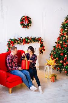 Mädchen öffnet begeistert weihnachtsgeschenk, während sie auf einem roten sofa sitzt und ihr freund sie beobachtet. gemütliches zimmer mit dekoriertem kamin und weihnachtsbaum