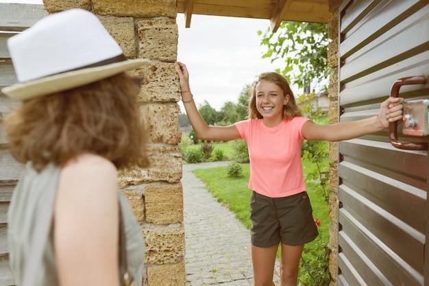 Mädchen öffnet die haustür, freundinnen begrüßt