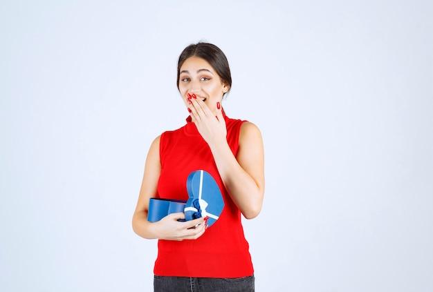 Mädchen öffnet eine blaue geschenkbox und wird überrascht.