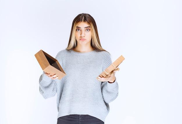 Mädchen öffnete eine geschenkbox aus karton und sieht traurig aus.