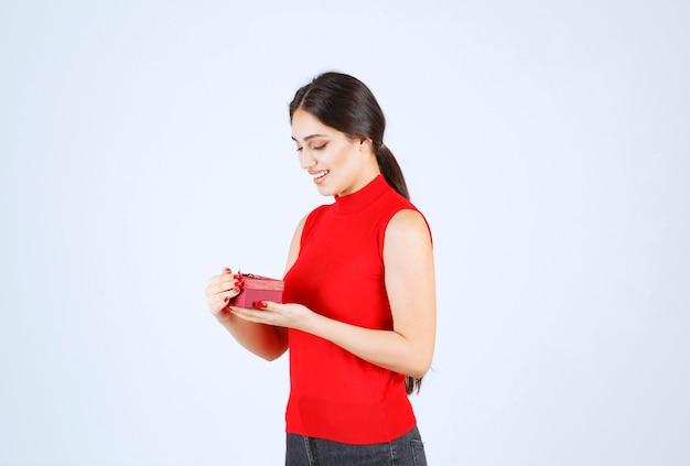 Mädchen öffnete eine rote geschenkbox und fühlt sich glücklich.