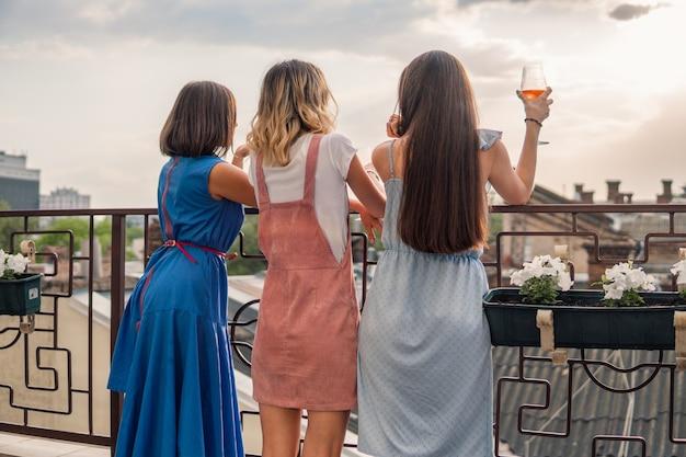 Mädchen party. frauen stehen auf dem balkon und schauen zu, trinken champagner