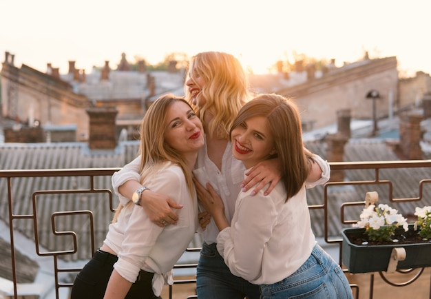 Mädchen party. schöne frauenfreundschaft auf dem balkon oder dach bei junggesellenabschied bei sonnenuntergang. sie umarmen sich