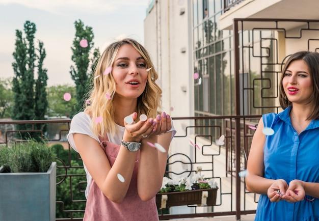 Mädchen party. schöne freundinnen auf dem balkon, die spaß bei der junggesellenabschied haben. braut bläst konfetti aus den händen