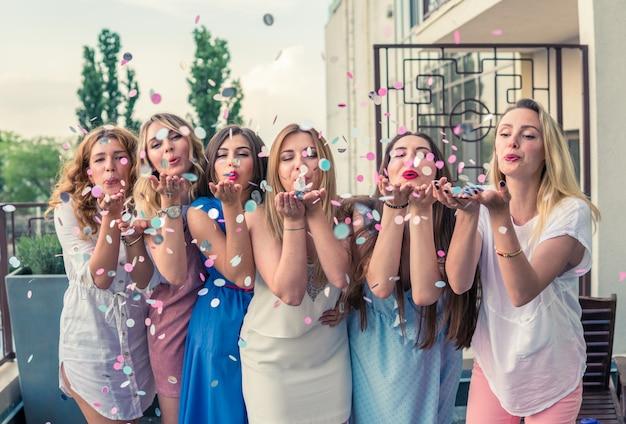 Mädchen party. schöne freundinnen auf dem balkon, die spaß bei der junggesellenabschied haben. sie blasen konfetti aus den händen. selektiver fokus