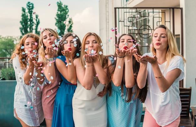 Mädchen party. schöne freundinnen auf dem balkon, die spaß bei der junggesellenabschied haben. sie blasen konfetti aus den händen