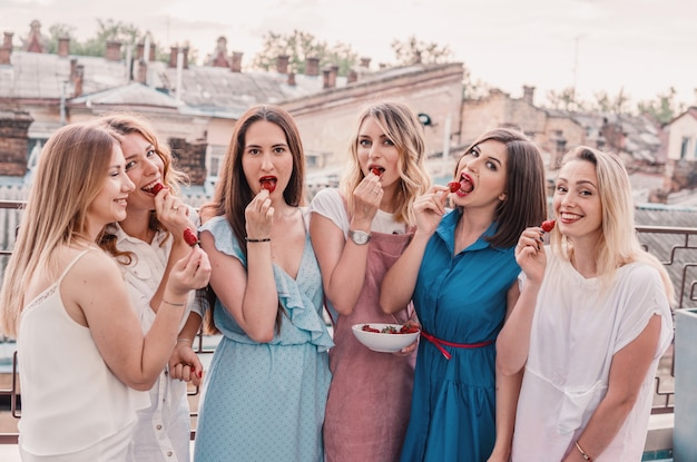 Mädchen party. schöne freundinnen auf dem balkon, die spaß bei der junggesellenabschied haben. sie essen erdbeere