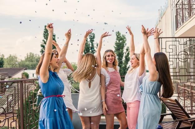 Mädchen party. schöne freundinnen auf dem balkon, die spaß bei der junggesellenabschied haben. sie tanzen in konfetti mit erhobenen händen