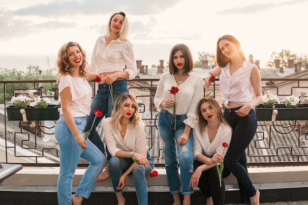 Mädchen party. schöne freundinnen auf dem balkon oder dach mit blumen bei junggesellenabschied. sie tragen die gleiche kleidung