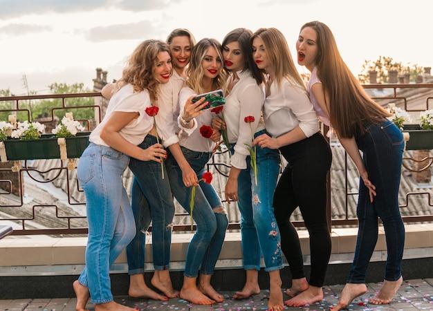 Mädchen party. schöne freundinnen auf dem balkon oder dem dach, die bei der junggesellenparty ein selfie mit blumen machen. sie tragen die gleiche kleidung