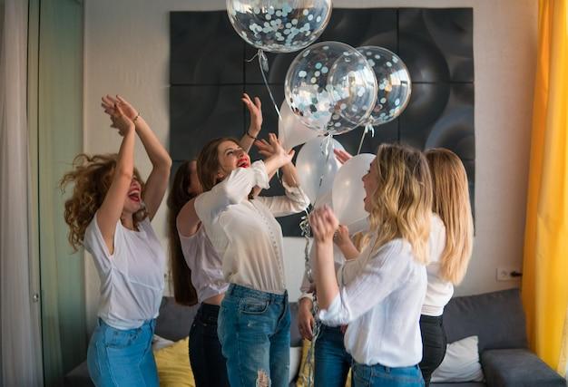 Mädchen party. schöne freundinnen bei junggesellenabschied. sie tanzen mit ballons.