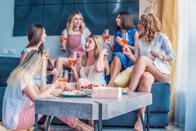 Mädchen party. schöne freundinnen, die spaß an der junggesellenabschied haben. sie feiern und trinken champagner beim junggesellinnenabschied. selektiver fokus auf lebensmittel.