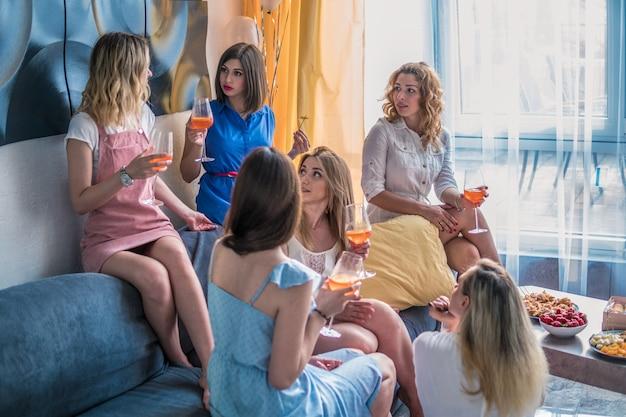 Mädchen party. schöne freundinnen, die spaß an der junggesellenabschied haben. sie feiern und trinken champagner beim junggesellinnenabschied. sie reden