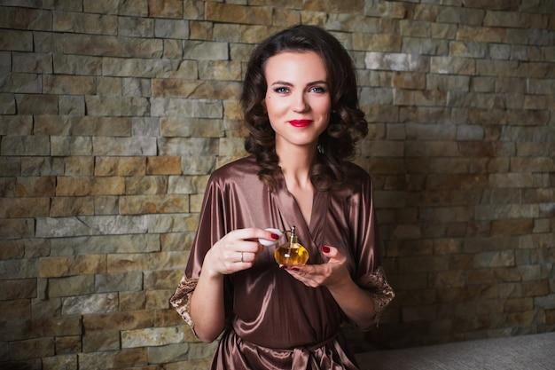 Mädchen pinup mit dem brunettehaar und retro- make-up mit den roten lippen in einem bademantel auf einer dunkelheit. mädchen sitzt auf dem bett. weinlesebild. frau mit parfümflasche