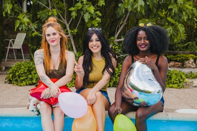 Mädchen posieren mit ballons am pool