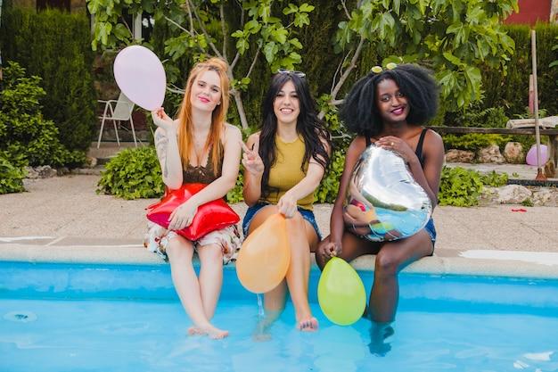 Mädchen posieren und lächeln in den pool