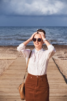 Mädchen posiert am strand gegen das meer.
