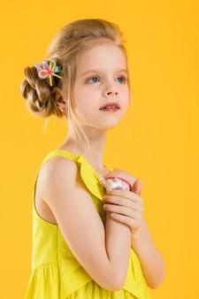 Mädchen posiert auf gelbem grund.