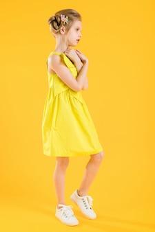 Mädchen posiert auf gelbem kleid.