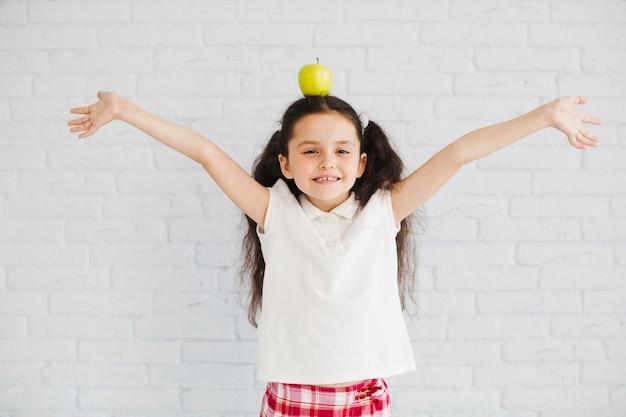 Mädchen posiert mit apfel auf kopf