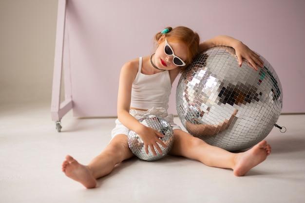 Mädchen posiert mit discokugel und sonnenbrille