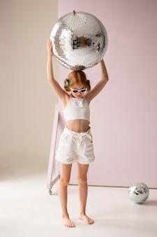 Mädchen posiert mit discokugel voller schuss