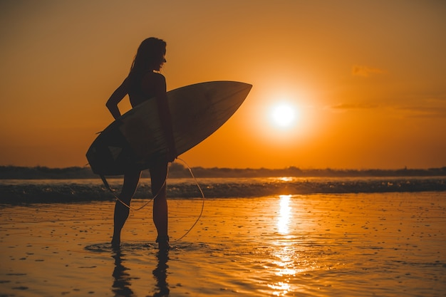 Mädchen posiert mit einem brett bei sonnenuntergang