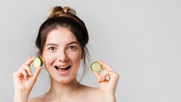 Mädchen posiert mit gurkenscheiben