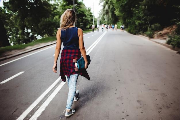 Mädchen posiert mit skateboard