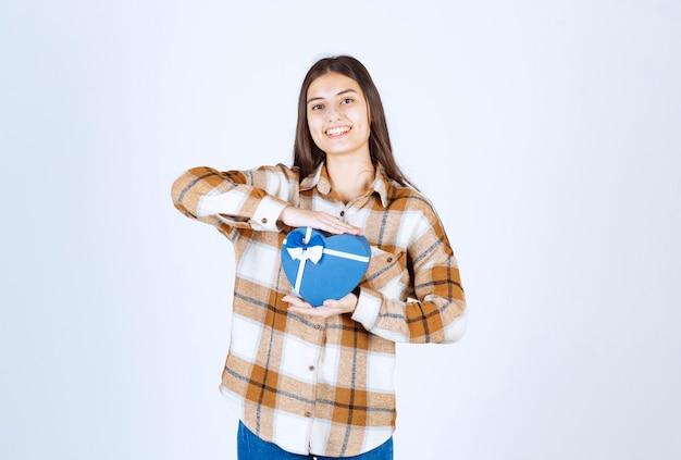 Mädchen posiert mit überraschungsgeschenk auf weißer wand.