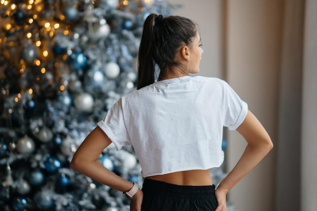 Mädchen posiert vor dem hintergrund des weihnachtsdekors.