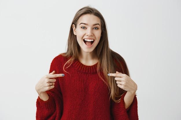 Mädchen prahlt mit ihrem erfolg. wir sehen eine aufgeregte, glückliche geschäftsfrau in einem trendigen, losen pullover, die mit den zeigefingern auf die brust zeigt und breit lächelt, während sie erzählt, was positiv passiert ist