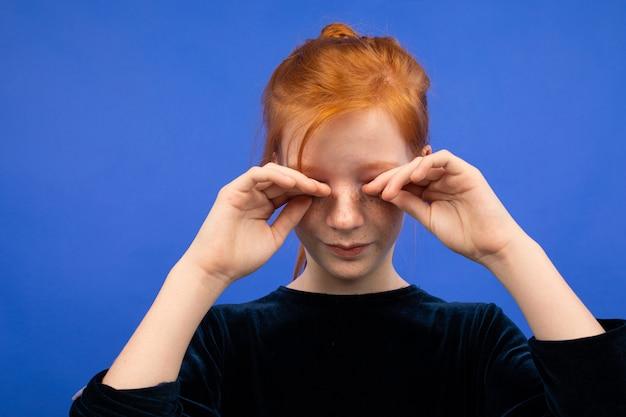 Mädchen reibt sich die augen wegen trockenheit auf blau
