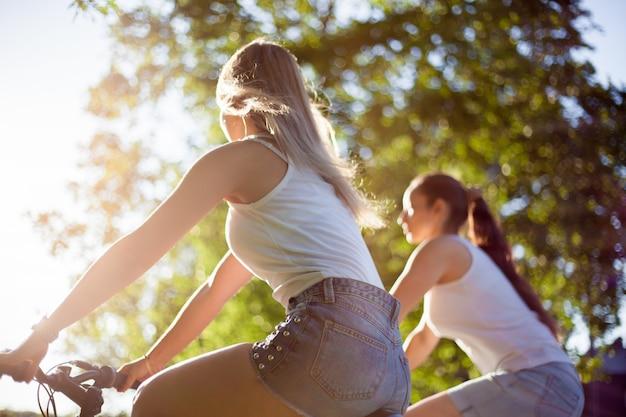 Mädchen reiten fahrrad und sonne in ihren gesichtern