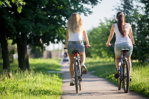 Mädchen reitet auf einem fahrrad von hinten