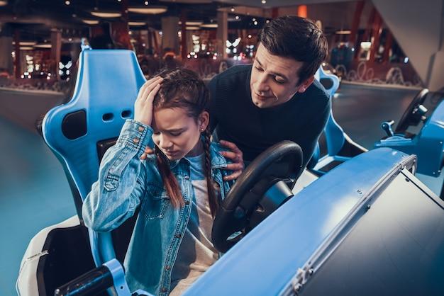 Mädchen reitet blaues auto im säulengang tochter verliert