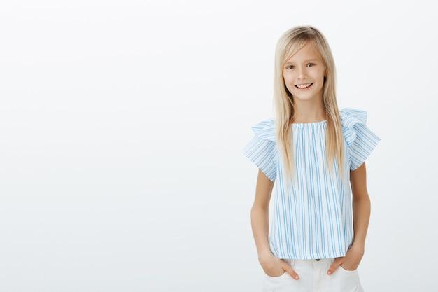 Mädchen rettete katze vom baum und fühlte sich stolz. nettes kleines blondes kind in der stilvollen bluse, händchen haltend in den taschen und breit lächelnd, mit lieblingslehrer über gute noten sprechend, über graue wand stehend