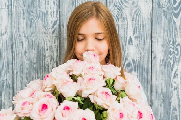 Mädchen riechender blumenstrauß der rosen
