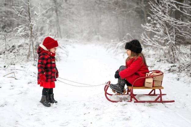 Mädchen rodeln an einem frostigen, verschneiten tag mit geschenken im wald