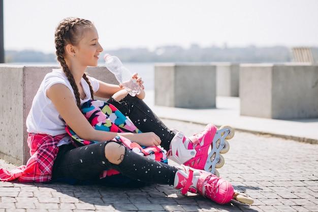 Mädchen rollschuhlaufen und trinkwasser