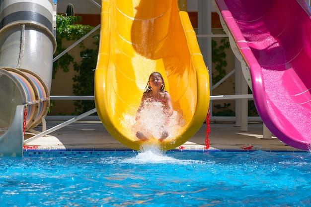 Mädchen rollt die wasserrutschen am wasserpark herunter
